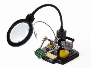 Derde hand met vergrootglas en soldeerstation